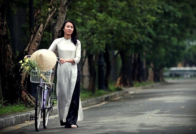 Mujer vietnamita con bicicleta y sombrero cónico